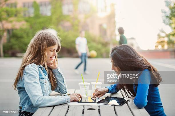 Side view of female teenagers using digital tablet at table outdoors