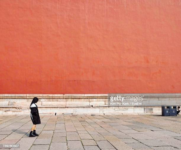 Side View Of Female Tourist Standing Against Orange Wall At Forbidden City