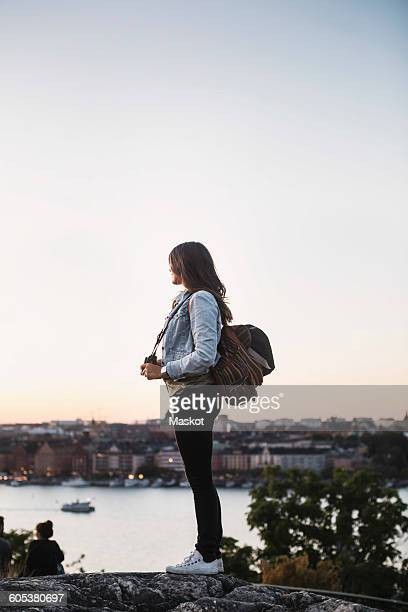 Side view of female tourist standing on rock against clear sky