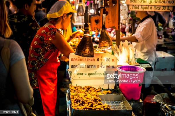 Side View Of Female Vendor Selling Food At Night Market