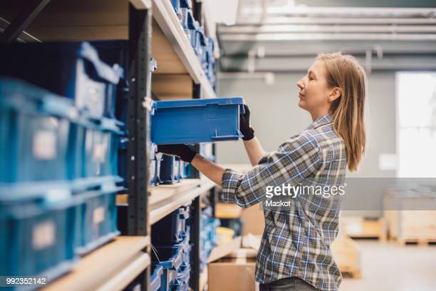 Side view of female worker keeping blue crate on rack at warehouse