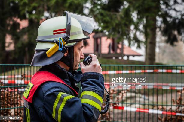 side view of firefighter standing by fence - hoofddeksel stockfoto's en -beelden