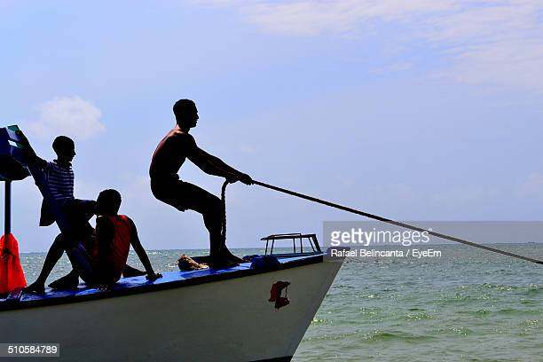 Side view of fisherman pulling rope on boat