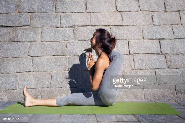 Side view of flexible woman doing yoga on sidewalk against stone wall