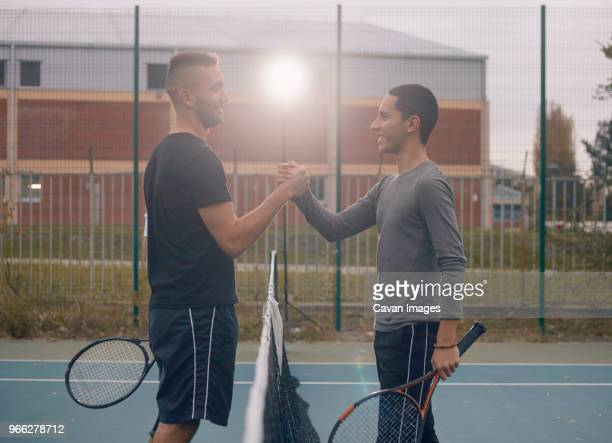 side view of friends holding hands while playing badminton - badminton sport stock pictures, royalty-free photos & images