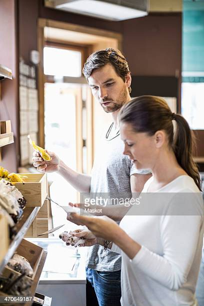 Side view of friends reading label in supermarket
