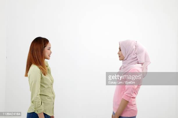 side view of friends standing face to face against white background - three quarter length stock pictures, royalty-free photos & images