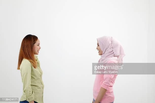 side view of friends standing face to face against white background - 宗教的なベール ストックフォトと画像