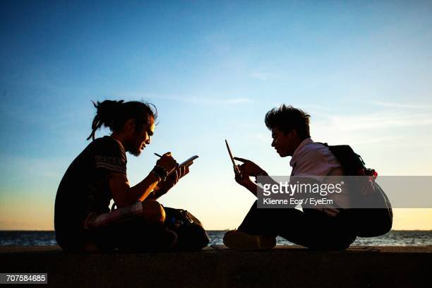 Side View Of Friends Using Technology On Retaining Wall By Sea