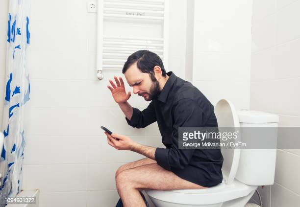 side view of frustrated man gesturing while using smart phone on toilet seat - defecare foto e immagini stock
