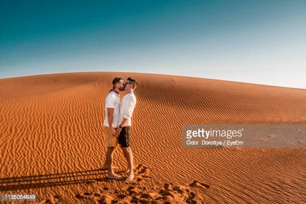 side view of gay couple kissing while standing at desert against blue sky - beautiful gay men photos et images de collection