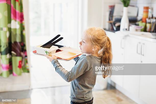 Side view of girl carrying food tray in preschool