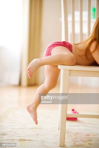 Side view of girl climbing chair