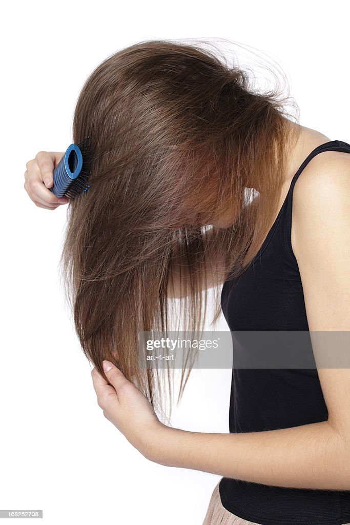 Side view of girl combing hair : Stock Photo