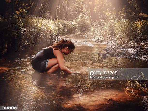 side view of girl crouching in stream - heather brooke ストックフォトと画像
