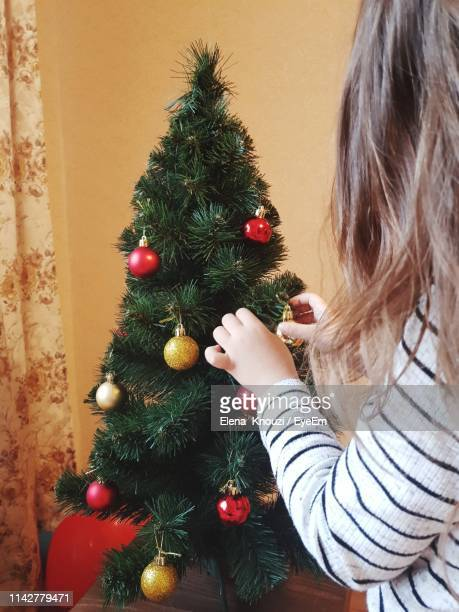 side view of girl decorating christmas tree at home - elena knouzi stock pictures, royalty-free photos & images