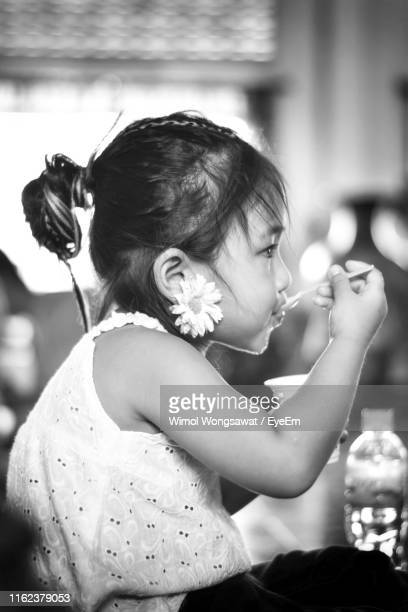 side view of girl eating food indoors - wimol wongsawat stock photos and pictures