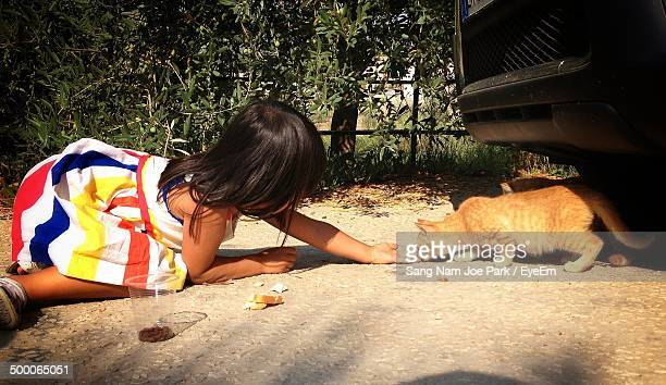 Side view of girl feeding cat outdoors