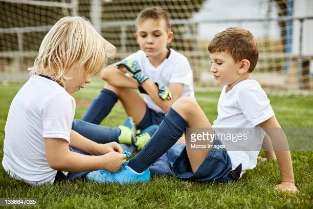 side view of girl helping boy tie shoe in soccer field - team sport stock pictures, royalty-free photos & images