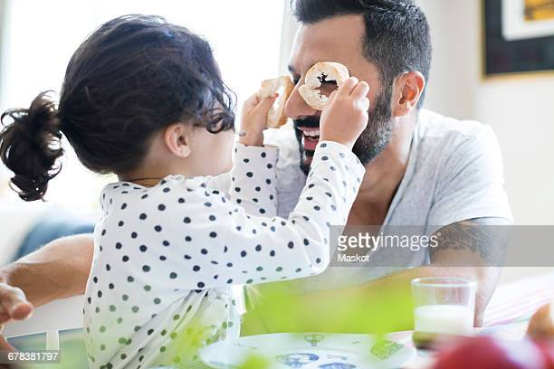 Side view of girl holding bread slices playing with father at table