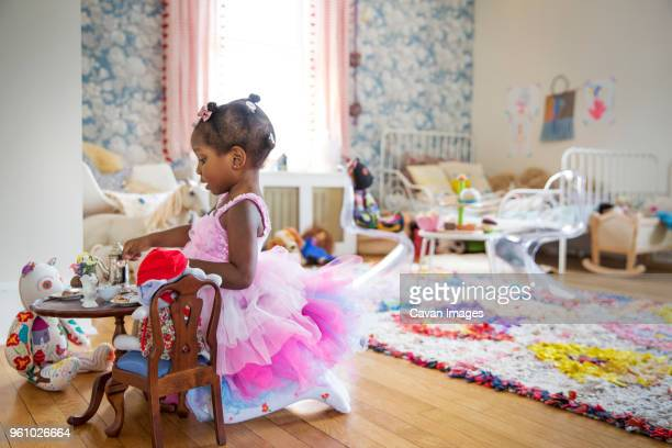 Side view of girl in pink dress having a tea party