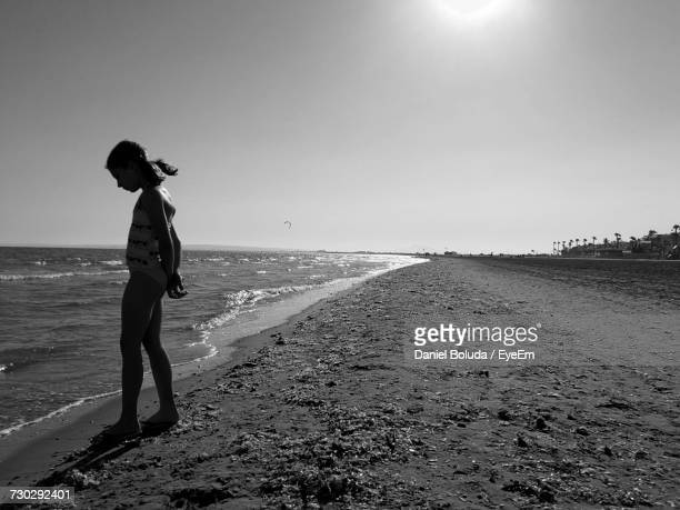 Side View Of Girl In Swimsuit Standing On Shore At Beach Against Clear Sky