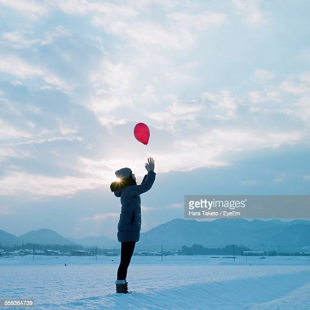 Side View Of Girl In Warm Clothing Catching Red Balloon While Standing On Snowy Field