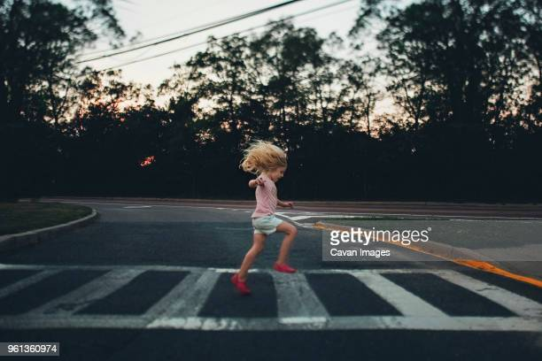 side view of girl jumping on zebra crossing against trees - zebra crossing stock pictures, royalty-free photos & images