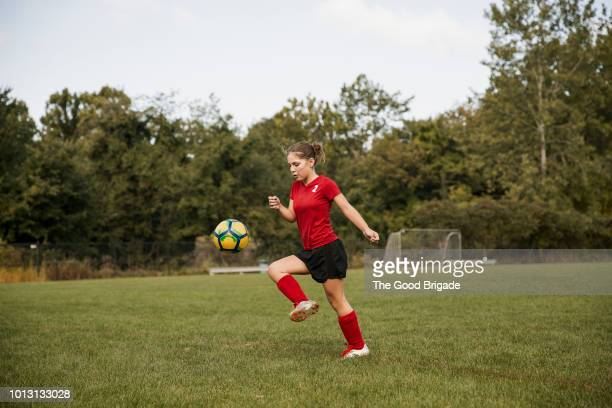 side view of girl kicking soccer ball on field - american football sport photos et images de collection