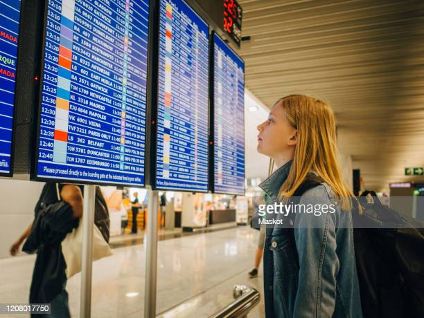 side view of girl looking at departure board while standing at airport - digital viewfinder stock pictures, royalty-free photos & images