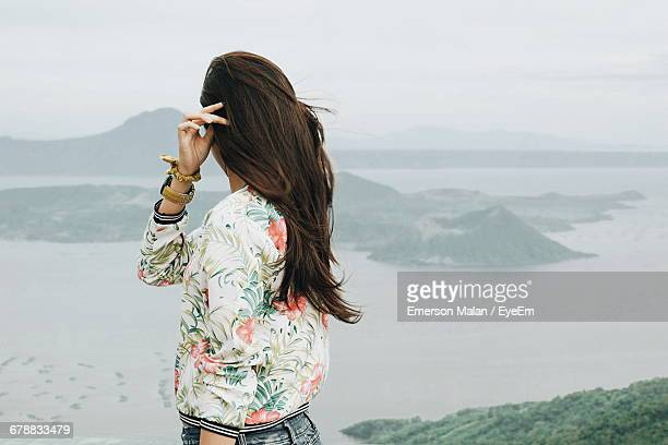 side view of girl looking at view of taal volcano island - taal volcano stock photos and pictures