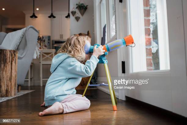 side view of girl looking through telescope while kneeling by door at home - telescope stock pictures, royalty-free photos & images