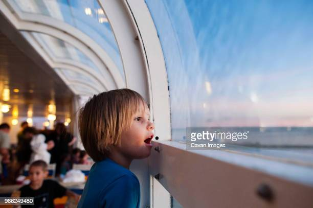 side view of girl looking through window while traveling in cruise ship - kreuzfahrtschiff stock-fotos und bilder