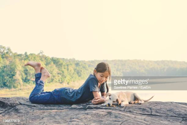 side view of girl lying by puppy on rock against lake - dog eats out girl stock pictures, royalty-free photos & images