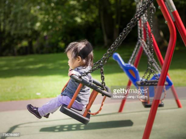 Side View Of Girl On Swing In Park