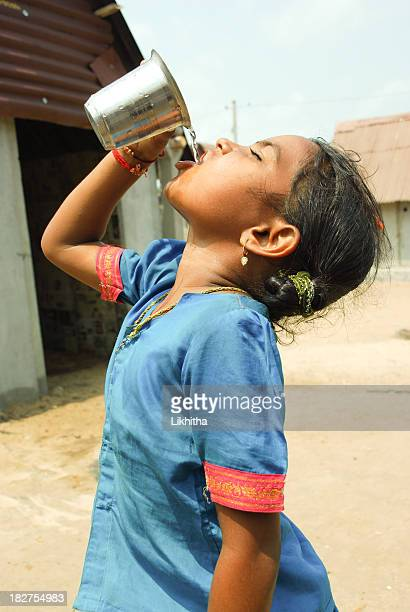 side view of girl outdoors drinking water out of metal cup - hot indian girls stock photos and pictures