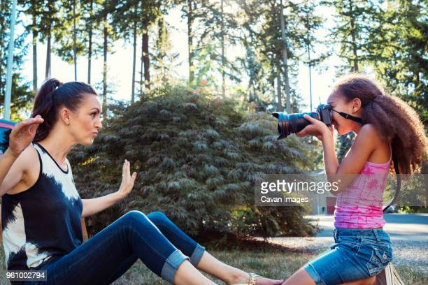 side view of girl photographing mother sitting on field in yard - cavan images foto e immagini stock
