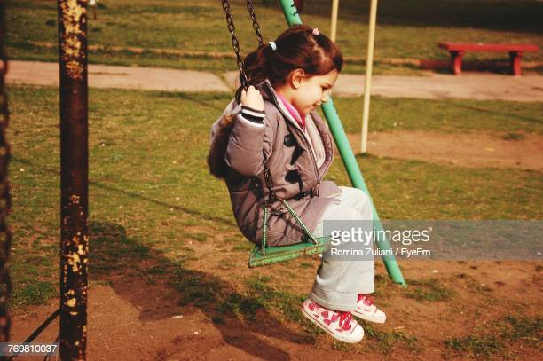Side View Of Girl Playing On Swing At Park