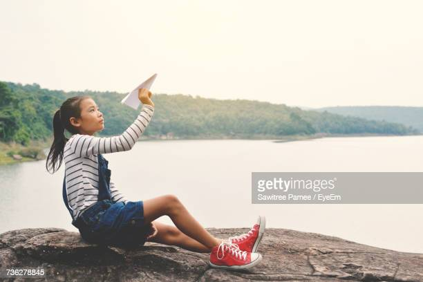 side view of girl playing with paper airplane while sitting on rock against lake - paper airplane stock pictures, royalty-free photos & images