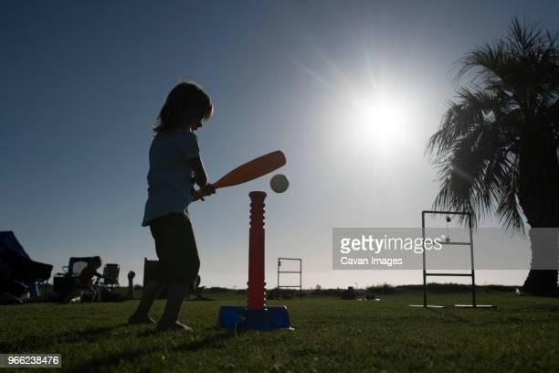 side view of girl playing with t-ball at park during summer - バッティング ストックフォトと画像