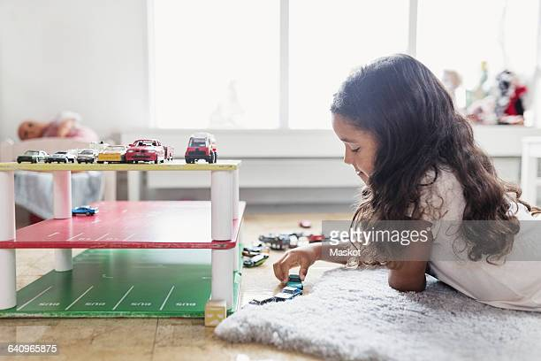 side view of girl playing with toy car in day care center - toy car stock pictures, royalty-free photos & images