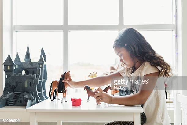 Side view of girl playing with toy horses at table