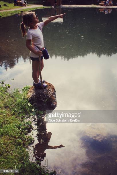 Side View Of Girl Pointing While Standing On Rock In Lake At Park