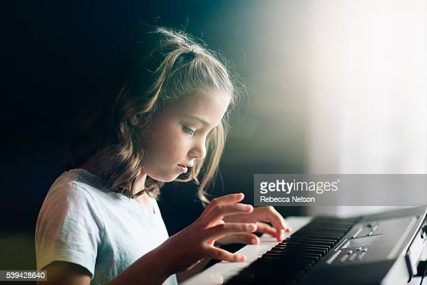 side view of girl practicing on her piano keyboard