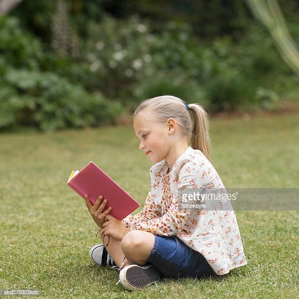 Side view of girl reading book in garden (8-9)