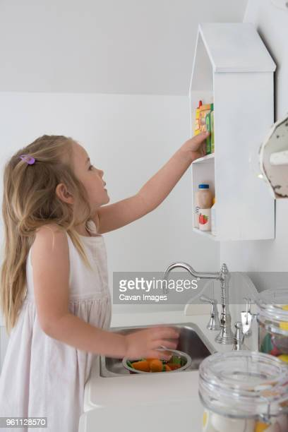 side view of girl removing bottle from shelf in playhouse - strip stock pictures, royalty-free photos & images