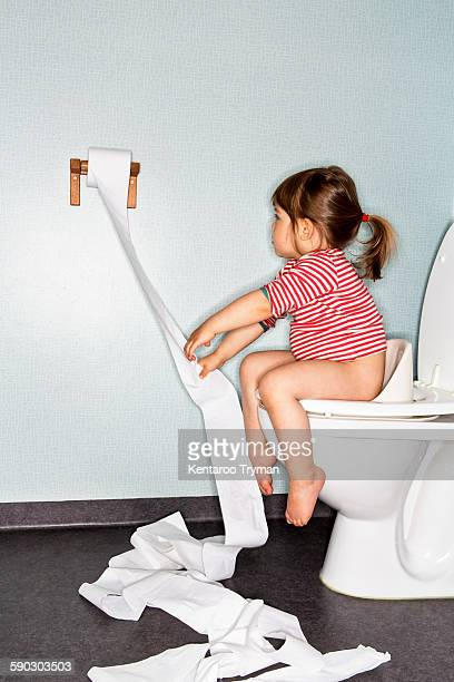 Side view of girl removing paper while sitting on toilet