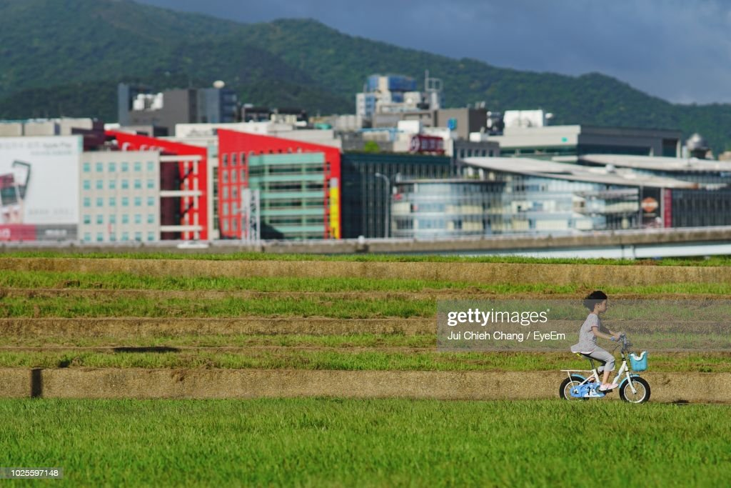 Side View Of Girl Riding Bicycle On Grassy Field Against Buildings : Stock Photo