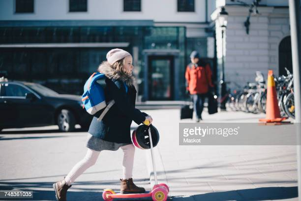 Side view of girl riding push scooter on city street during sunny day