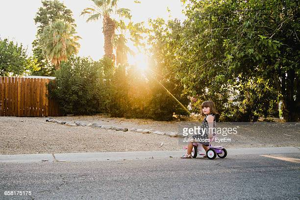 side view of girl riding tricycle on road - tricycle stock pictures, royalty-free photos & images